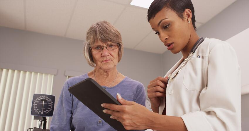 Doctor reviewing social security disability benefits with cancer records with patient